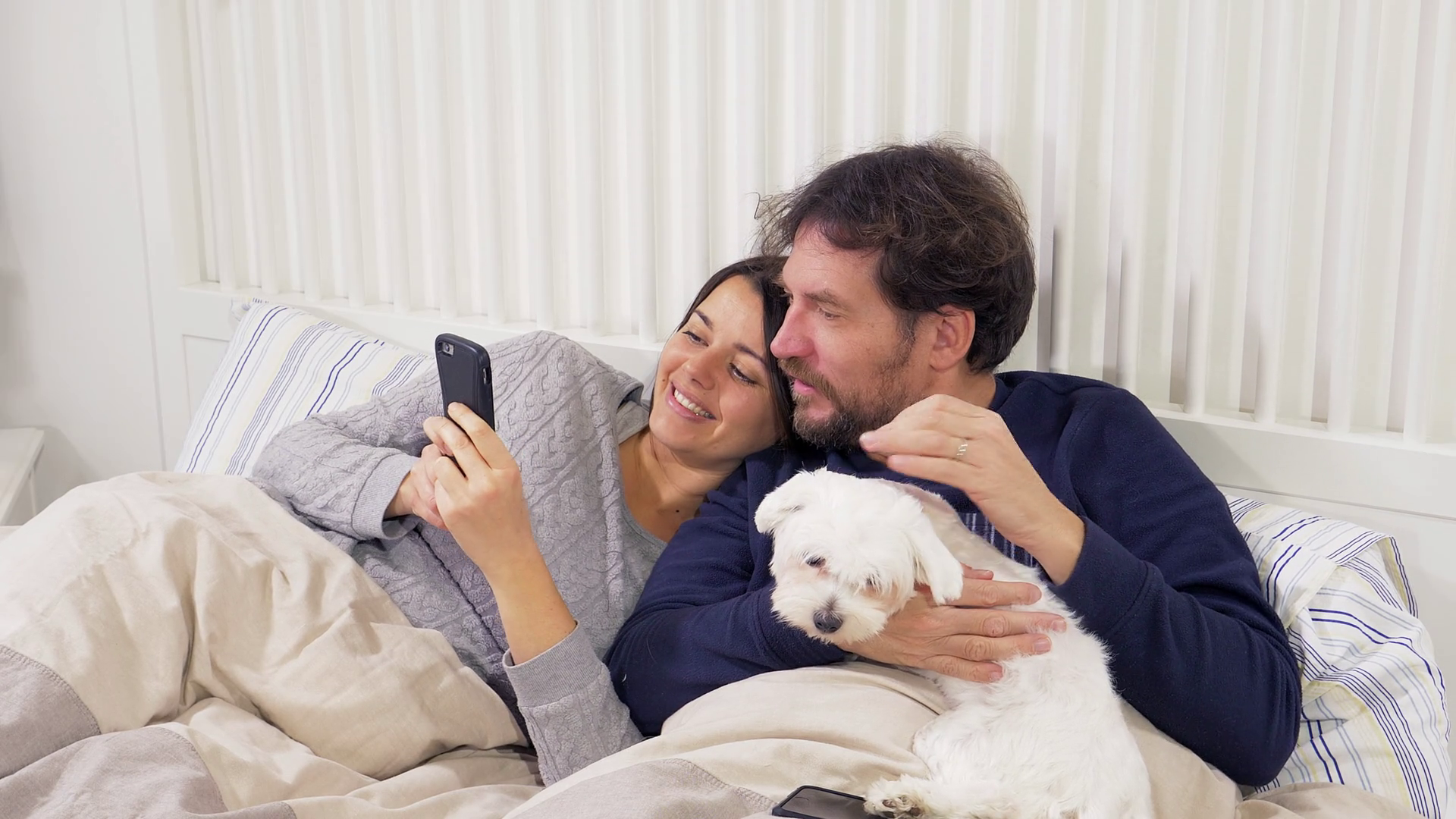 videoblocks-happy-couple-in-love-looking-pictures-on-phone-holding-dog_b0lerjyzhm_thumbnail-full05